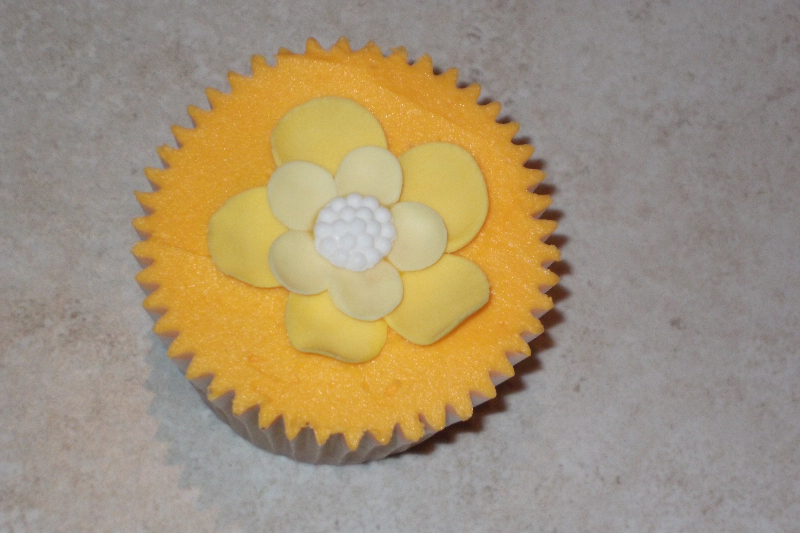 Vanilla cupcake with orange coloured butter cream with Yellow Flowers