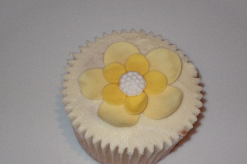 Vanilla Cupcake with white butter cream with a yellow flower