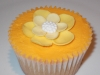 Vanilla cupcake with an Orange coloured, vanilla butter cream and a yellow flower